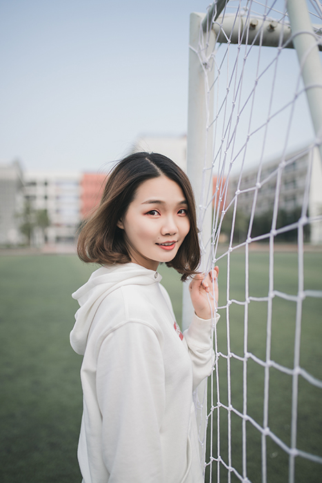 A female posing in front of goal posts