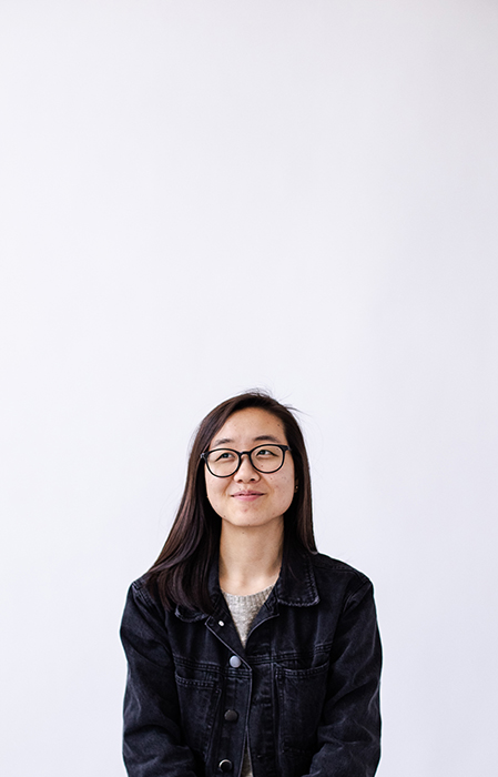 A cool profile photo of a girl posing against a white wall