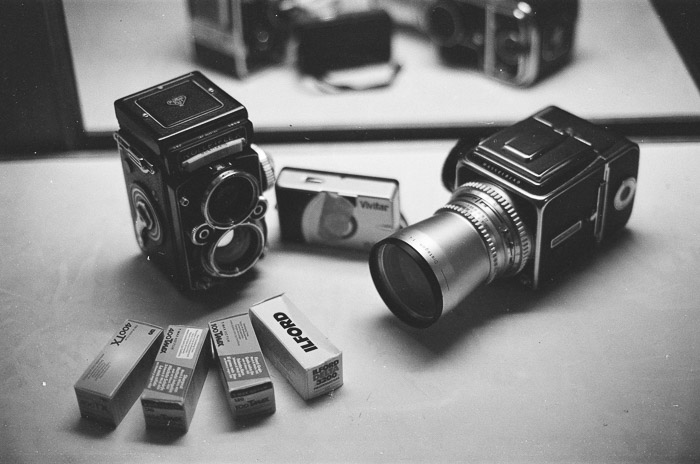 A black and white photo of two medium format film cameras