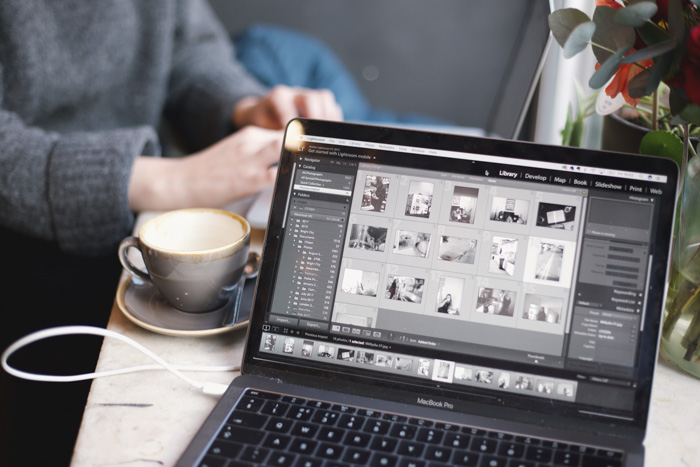 A close up of a person editing photos on light room, using dng file or RAW file format