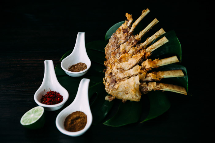 A restaurant photography shoot of a plate of food and spices against a dark background