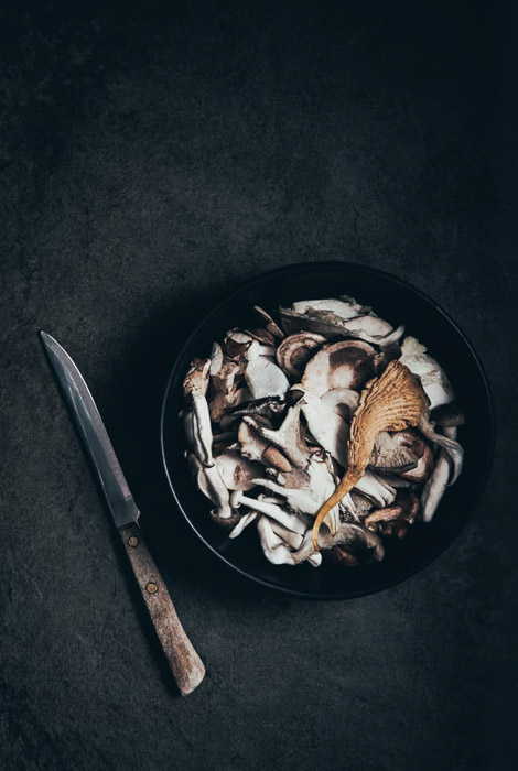 A dark and atmospheric fine art food photography still life ofmushrooms and a knife