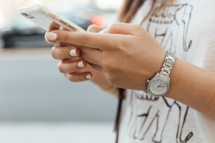 A close up of a girl accessing foap on her smartphone
