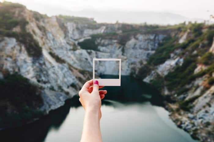 A person holding a square photo frame against a landscape