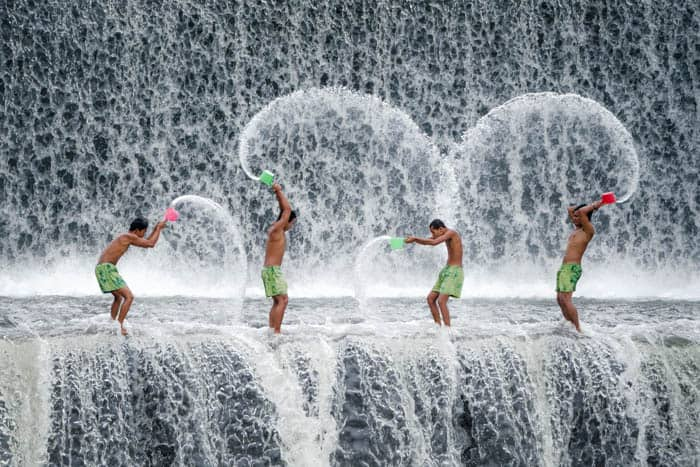 Four men throwing water in a waterfall - guide to becoming Instagram famous