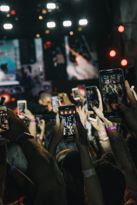 A concert photography shot of the audience all taking photos on their smartphone for Instagram profile pictures