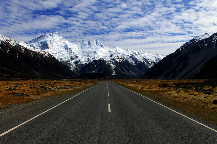 Road leading the eyes to snowy mountains through utilising leading line composition