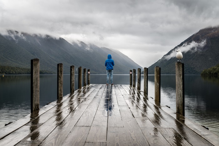 A man standing on a wooden pier