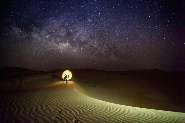 A photographer setting up an astrophotography shot in the desert