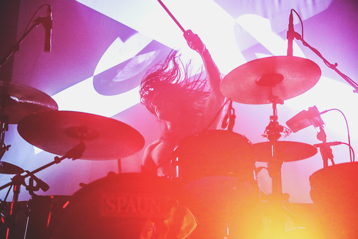 A concert photography shot of a drummer with distorted colors