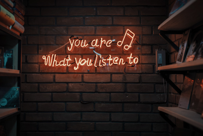 A neon sign on a brick wall, reading 'you are what you listen to - best photography podcast