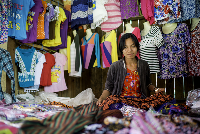 A female market vendor at her stall, with a busy cluttered background of colored material and clothes