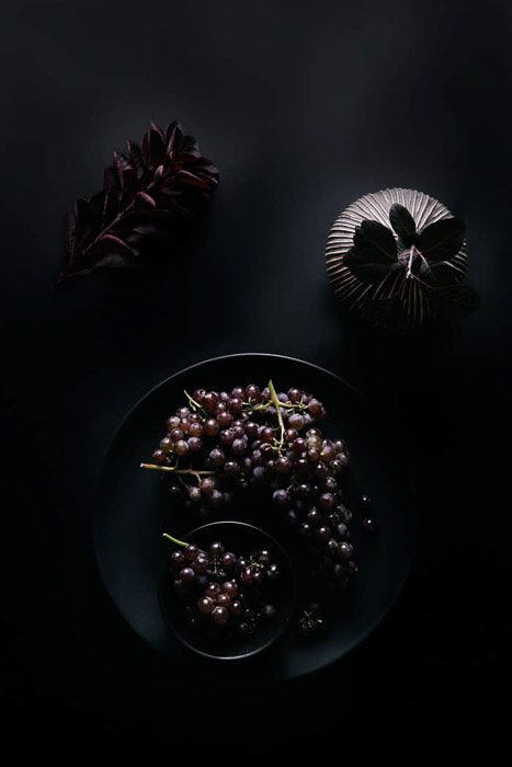 Overhead food shot of a bowl of grapes and other props on a dark background