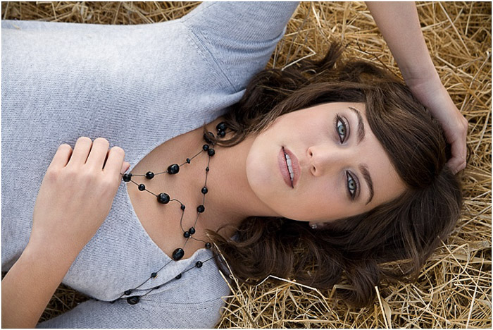 An overhead senior photography shot of a dark haired girl lying on straw