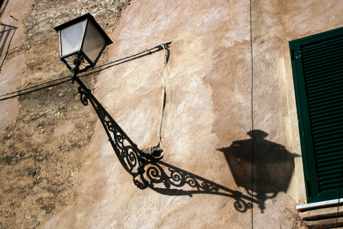 Street photo of a lantern with shadow cast on a stone wall