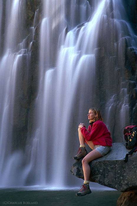 A female adventure photographer resting on a rock at Rainbow Falls, California