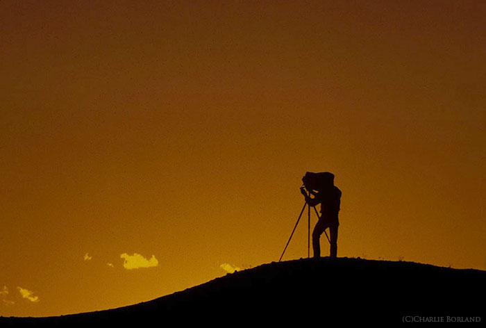 A silhouette of a solo adventure photographer against a sunset sky