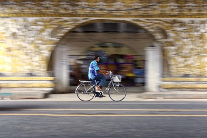 A man riding a bicycle through a tunnel