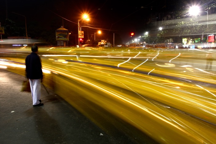 A person walking through a busy street at night using long exposure camera settings for street photography