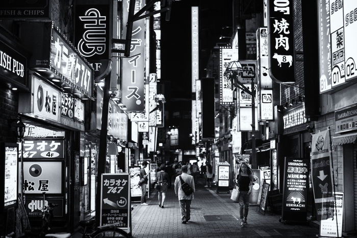 A black and white photo of a busy street scene in Tokyo