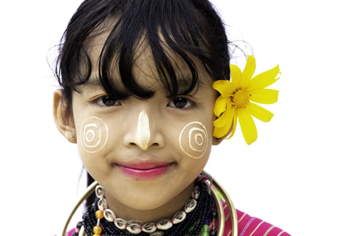 Close up portrait of a young girl in traditional face paint against a white portrait photo background