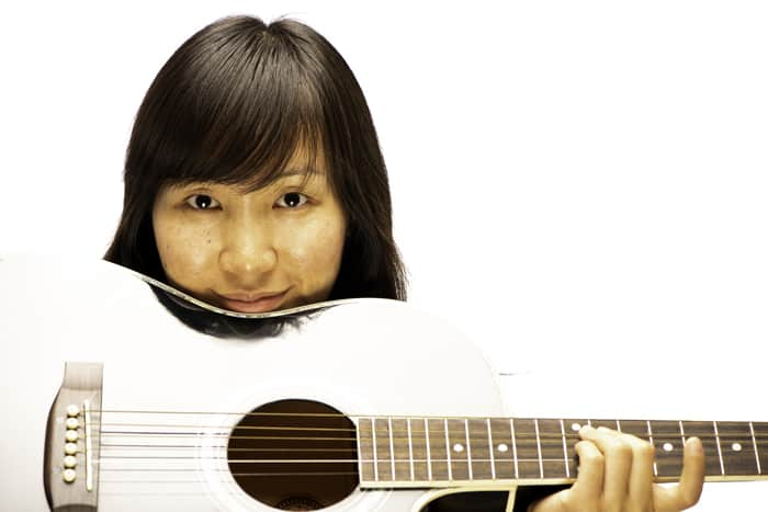 portrait of a female model holding a guitar against a white photography background