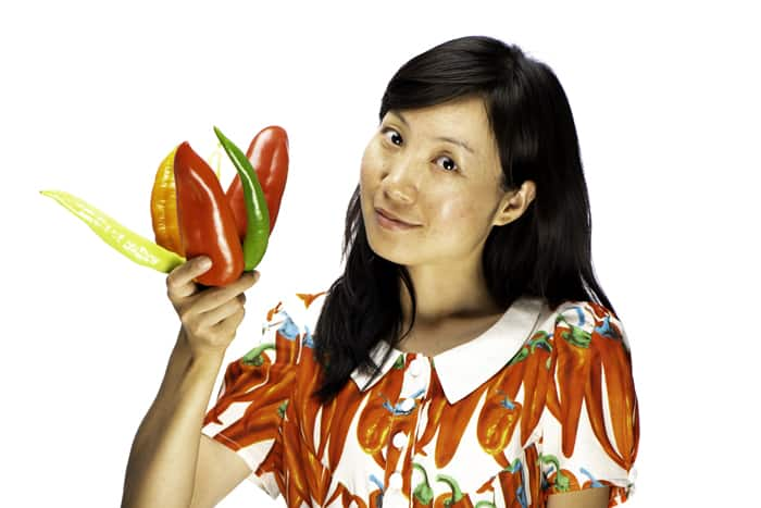 portrait of a female model holding chillis against a white photography background