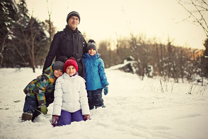 A sweet christmas picture of a family posing together in the snow