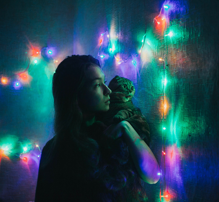 A nighttime portrait of a girl holding a cat surrounded by colorful Christmas lights