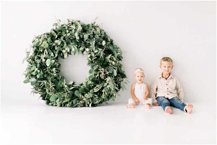 A minimalist christmas photo cards ideas of children posing by a giant christmas wreath
