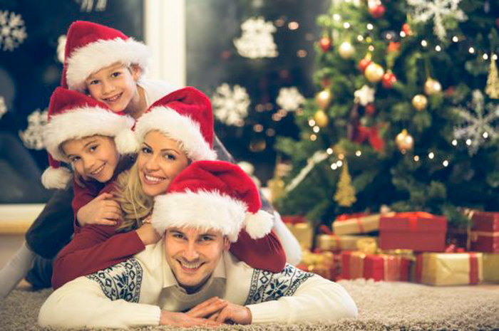 A family wearing christmas hats posing in a pile - christmas pictures ideas