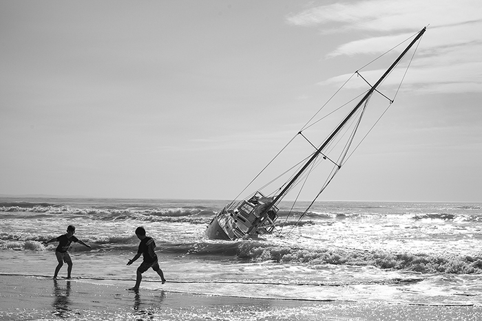 A monochrome shot of kids playing near a boat on New Brighton Beach, New Zealand., black and white photography tips