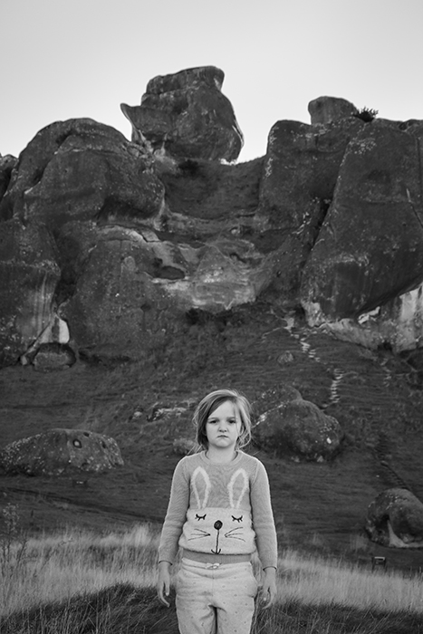 A child posing in front of rocks at at Castle Hill, New Zealand. Black and white photography tips