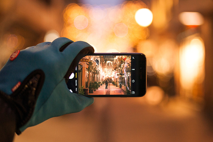 A person taking a smartphone photo of Christmas bokeh lights on a street