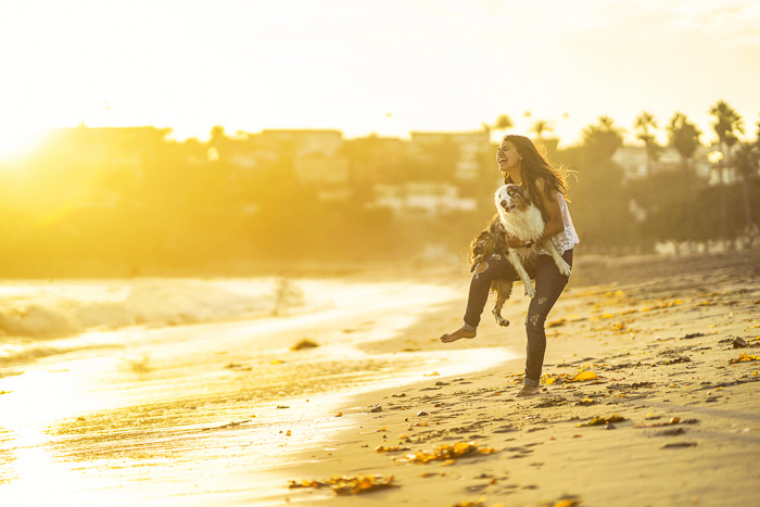 A woman and small dog on a beach shot with a Sony a7R II