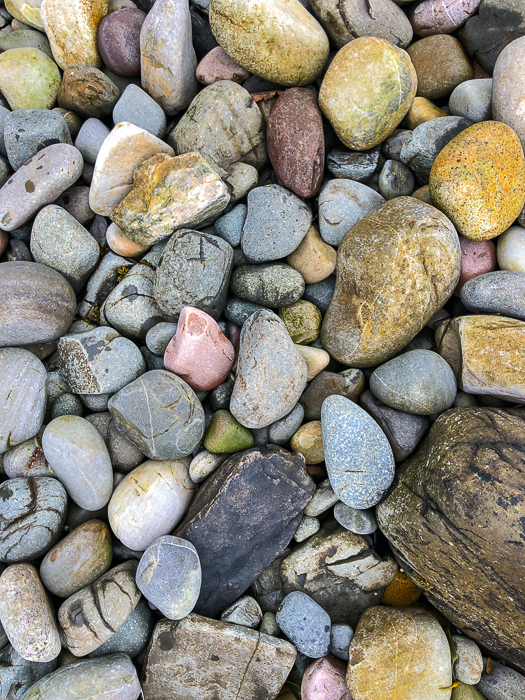 A close up photo of stones and pebbles on the beach