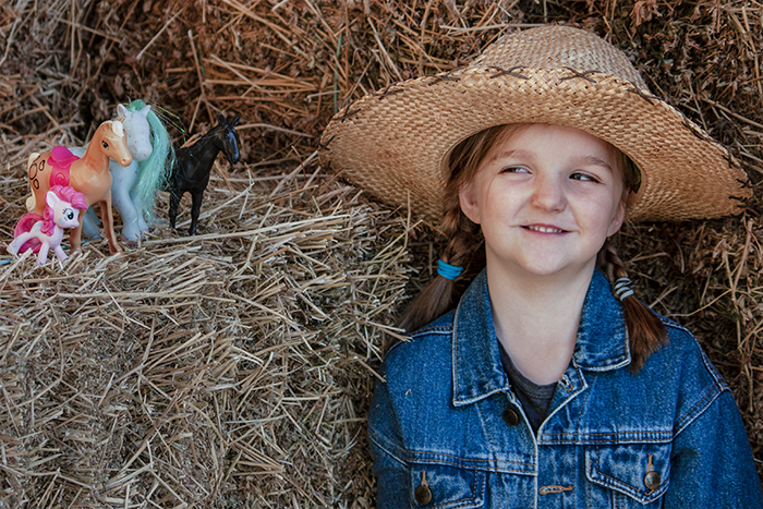 A young girl posing in a haybarn beside toy ponies