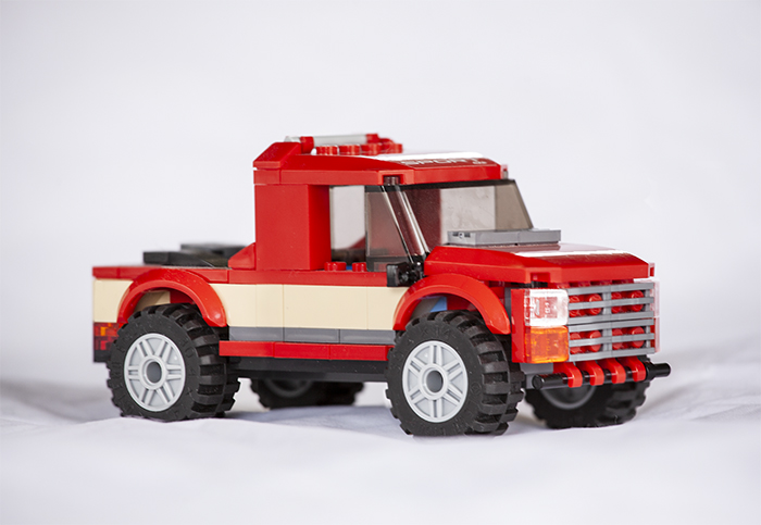Three photos of a red lego truck stacked so that more of the whole image is in focus.