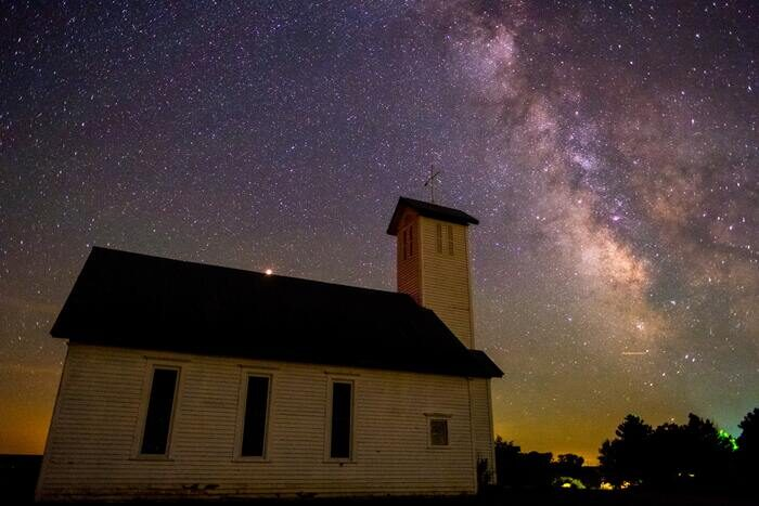 Foto de uma pequena igreja com a Via Láctea aparecendo no céu noturno