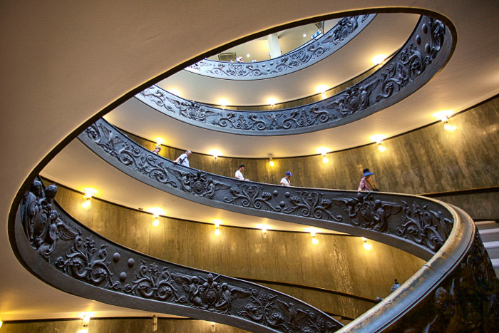 People walking down a spiral staircase in the interior of an impressive building