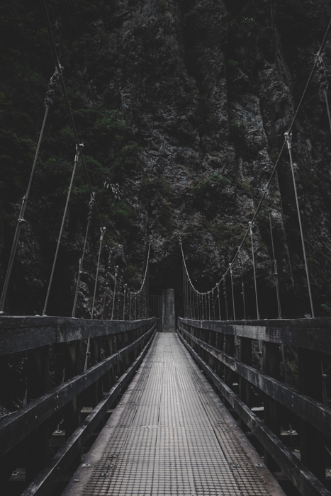 A large wooden bridge leading towards a mountain