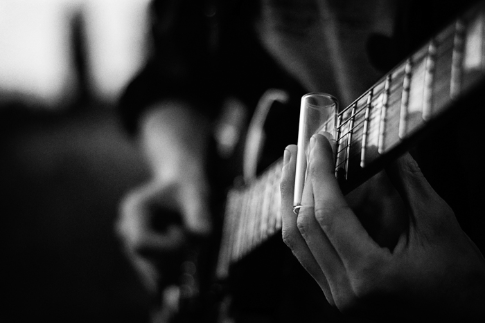 A grainy black and white close up of a person playing guitar