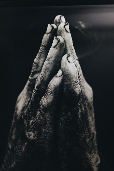 A black and white film photography close up of a person holding their two hands together in a 'praying' gesture