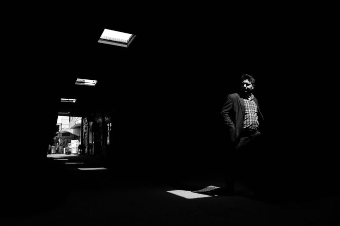 A street scene of a man walking through a passageway shot with black and white photography film