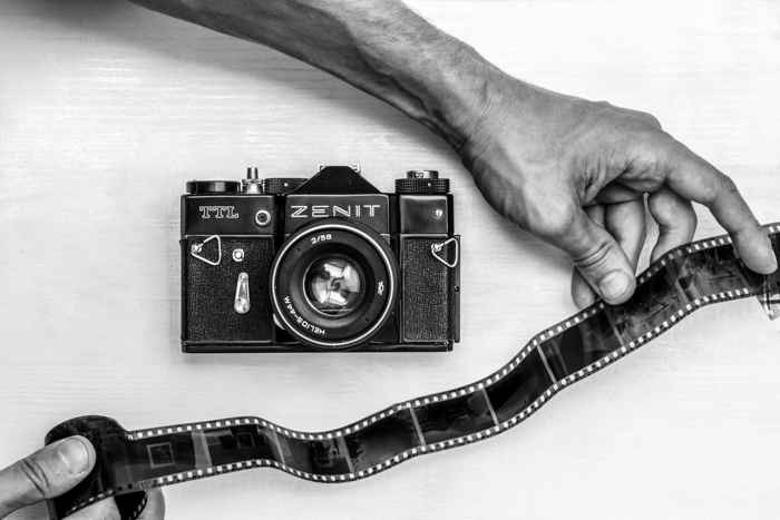 A flat lay of a zenit camera with a hand holding black and white film negative