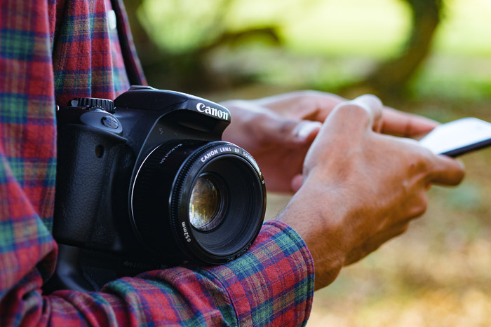 A close up of a photographer holding a camera and smartphone - where to buy dslr camera