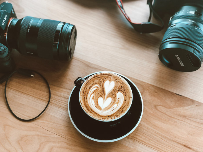 A cappucino on a wooden table with various DSLR camera - best camera stores