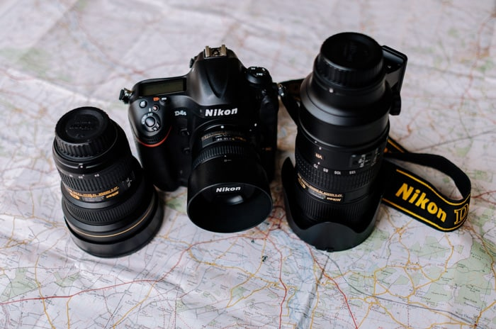 A Nikon full frame camera and two lenses resting on a map