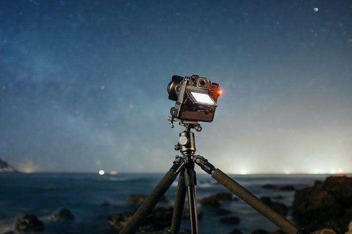 A DSLR camera set up on a tripod outdoors at night