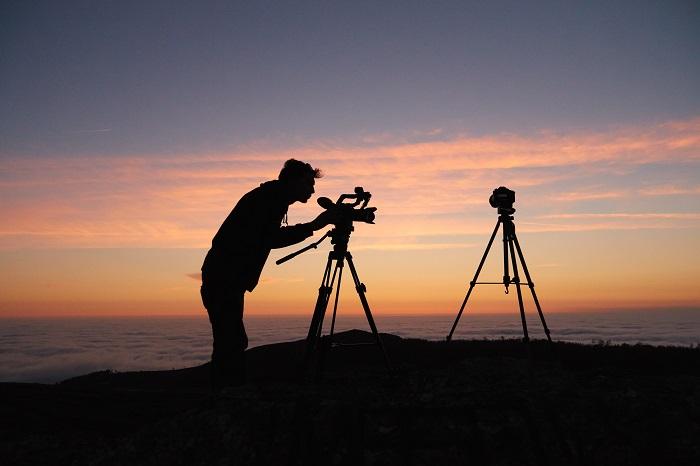 Silhueta de um fotógrafo fotografando com uma DSLR em um tripé ao pôr do sol